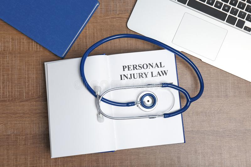 Book with words PERSONAL INJURY LAW. Stethoscope and laptop on wooden background, top view stock photos