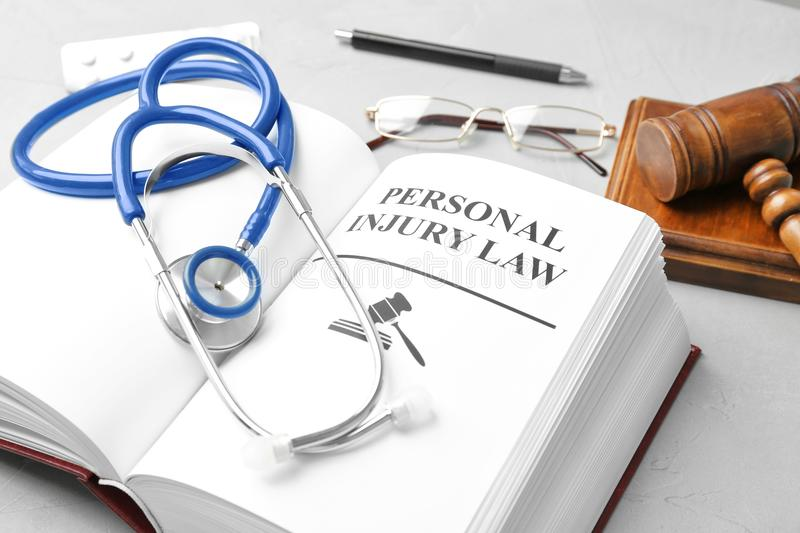 Book with words PERSONAL INJURY LAW. And stethoscope on table royalty free stock images