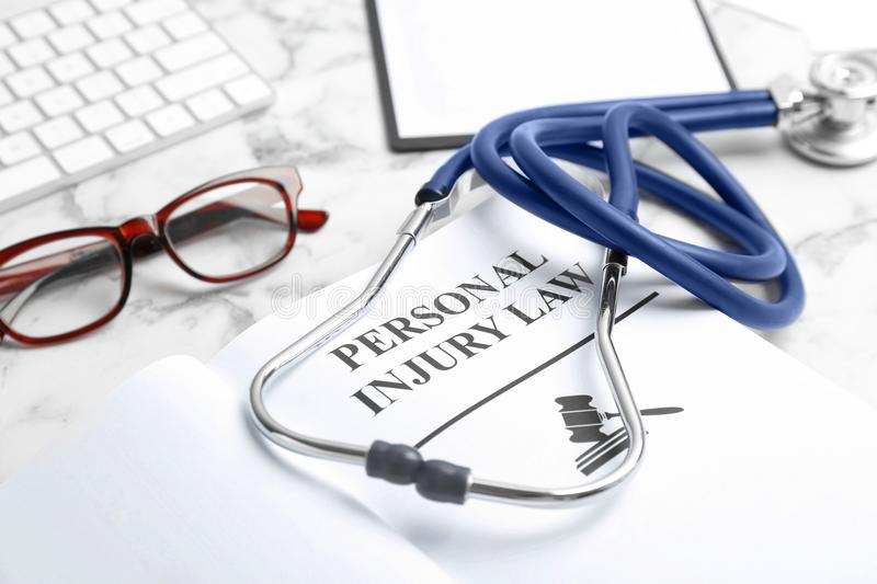Book with words PERSONAL INJURY LAW. And stethoscope on table, closeup royalty free stock photography