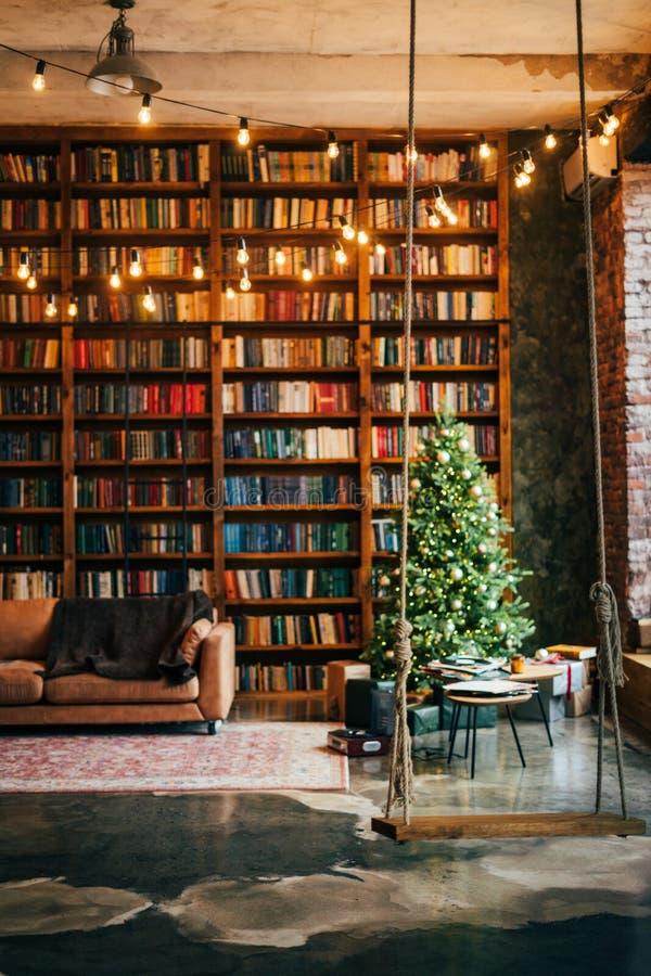Bookcase com as luzes da árvore de natal balançando sofá fotografia de stock royalty free