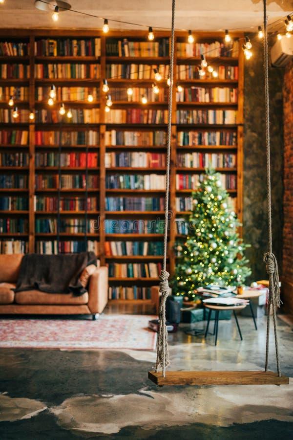 Bookcase com as luzes da árvore de natal balançando sofá imagens de stock royalty free