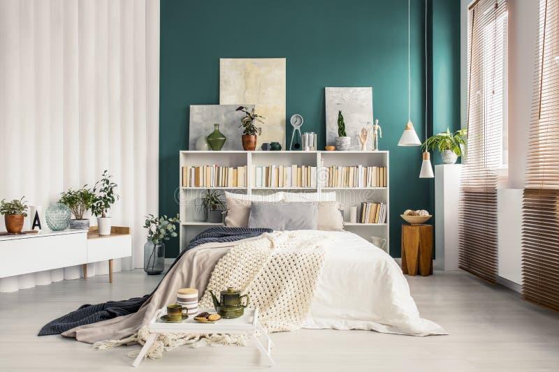 Bookcase headboard w zielonej sypialni obraz stock
