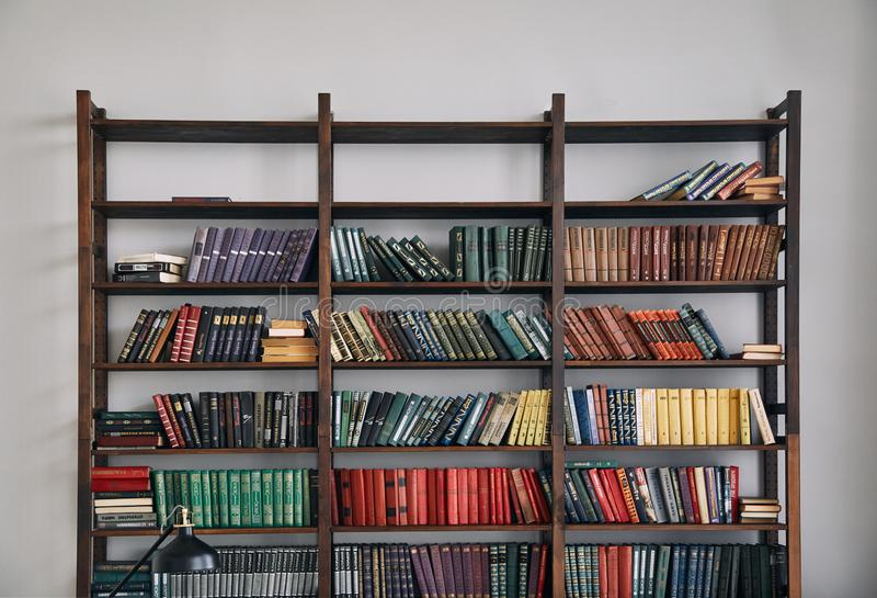 Bookcase with old books on the shelves royalty free stock photo