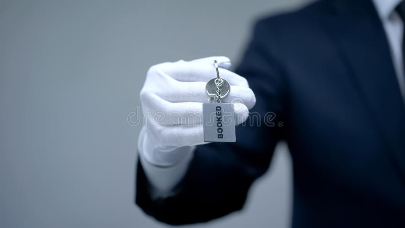 Booked word on keychain in receptionist hand, luxury hotel services, closeup. Stock photo royalty free stock images
