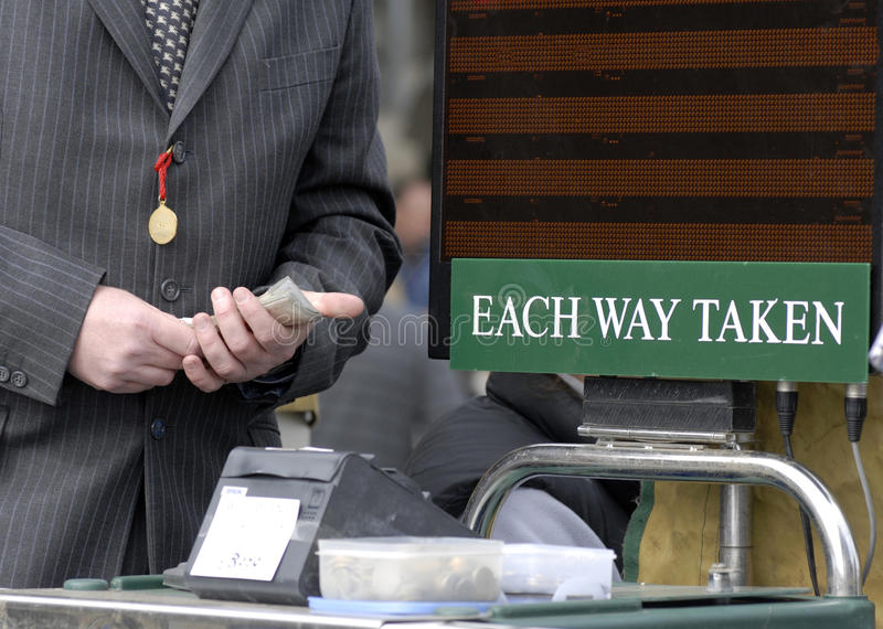 Bookie. Racecourse bookmaker wearing a suit with cash in hand stock image