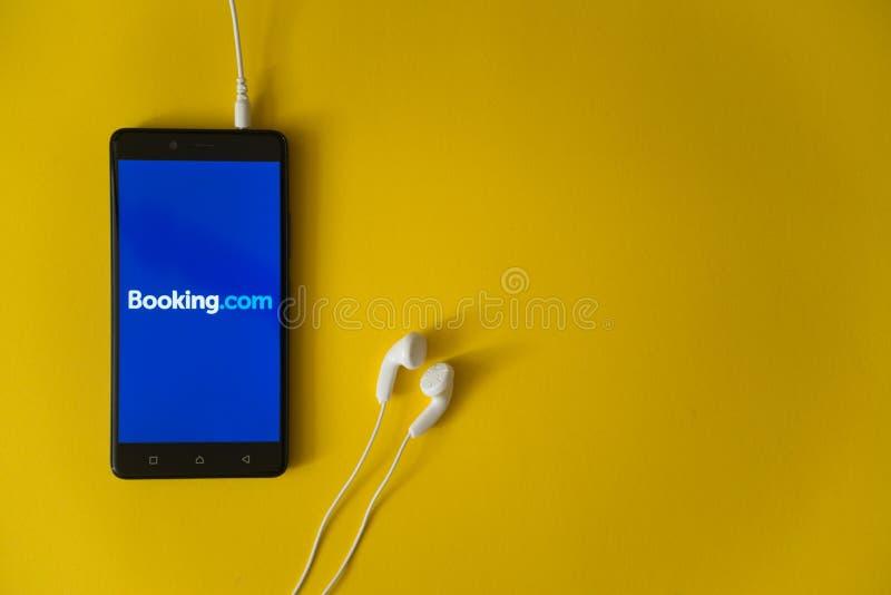booking Com-embleem op het smartphonescherm op gele achtergrond royalty-vrije stock fotografie
