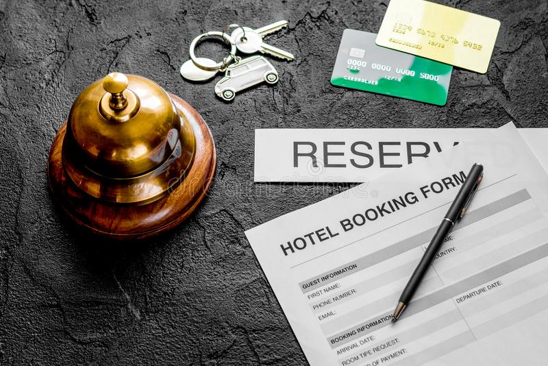 Booking form for hotel room reservation, pen and ring dark backg. Booking form for hotel room reservation, pen and ring on dark table background royalty free stock photos