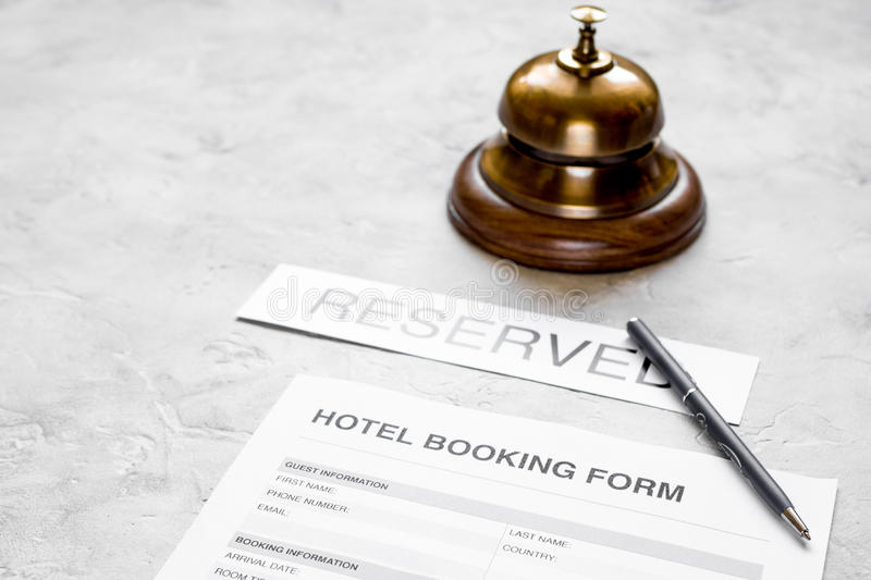 Booking form for hotel room reservation, pen and ring stone background. Booking form for hotel room reservation, pen and ring on stone table background stock photography