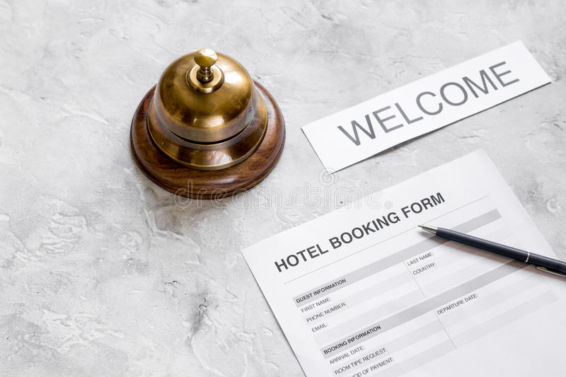 Booking form for hotel room reservation, pen and ring stone background. Booking form for hotel room reservation, pen and ring on stone table background stock photos