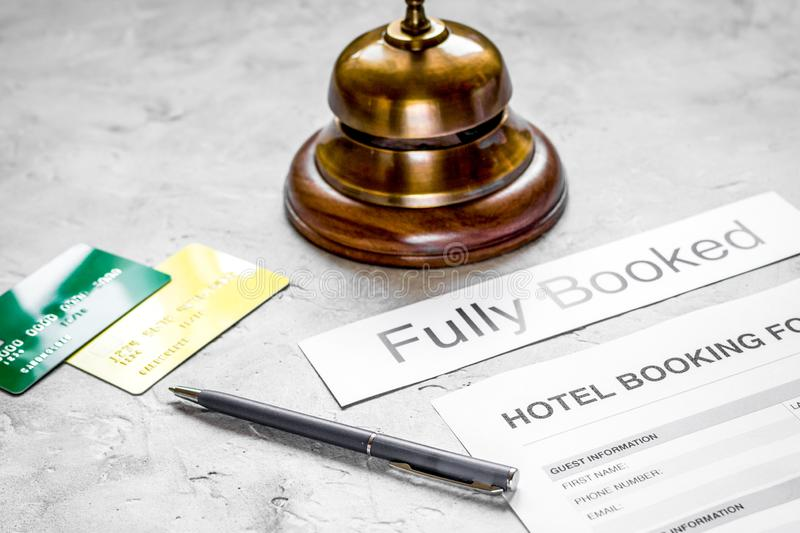 Booking form for hotel room reservation, pen and ring stone background. Booking form for hotel room reservation, pen and ring on stone table background royalty free stock photography