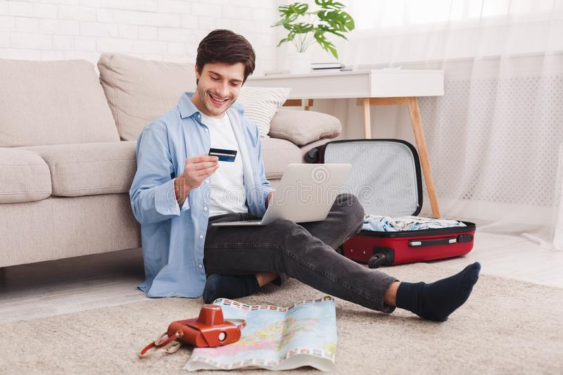 Booking tickets online. Man preparing for vacation, using laptop. Sitting on floor at home royalty free stock photo