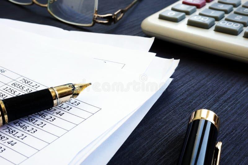 bookishly Финансовый отчет с диаграммами и калькулятором на столе стоковое изображение