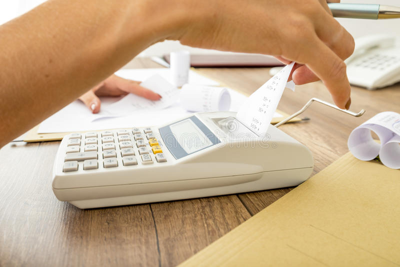 Bookkeeper doing calculations on an adding machine royalty free stock photography
