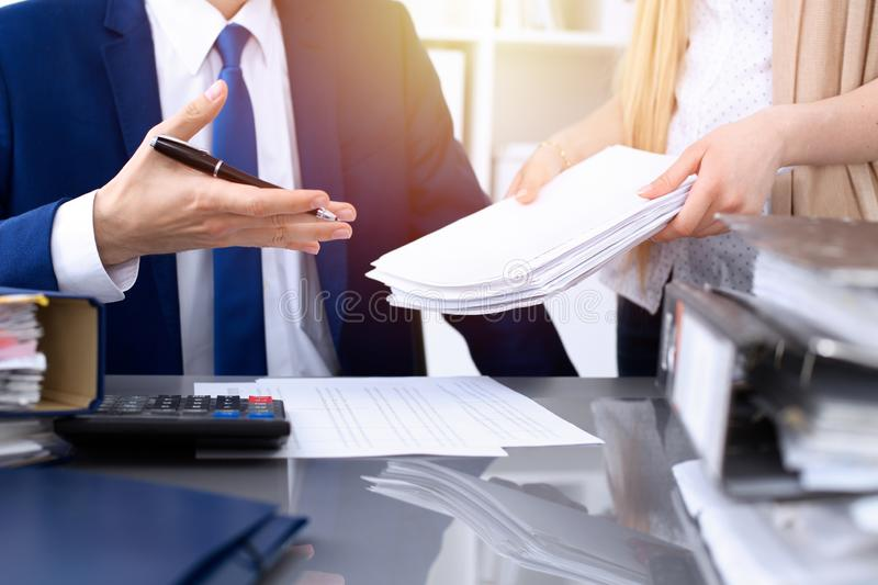 Bookkeeper or financial inspector hands making report, calculating or checking balance. Internal Revenue Service. Inspector man checking financial document royalty free stock image