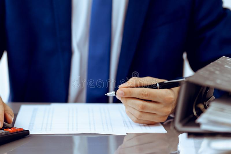Bookkeeper or financial inspector hands making report, calculating or checking balance. Internal Revenue Service. Inspector man checking financial document royalty free stock photography
