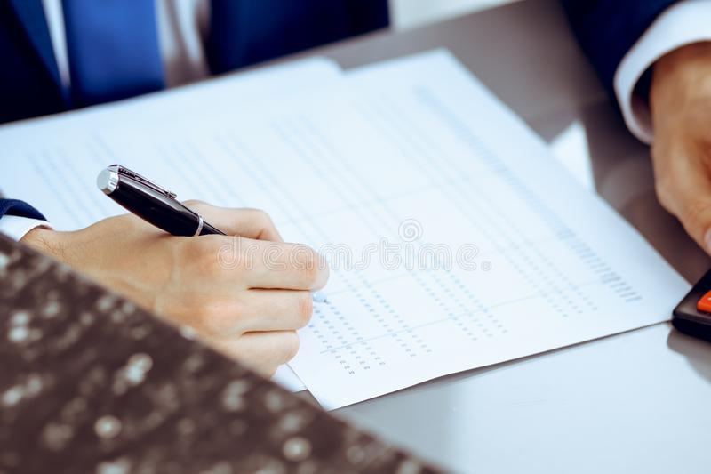 Bookkeeper or financial inspector hands making report, calculating or checking balance. Internal Revenue Service. Inspector man checking financial document royalty free stock photo