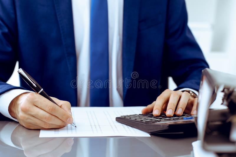 Bookkeeper or financial inspector hands making report, calculating or checking balance. Internal Revenue Service. Inspector man checking financial document royalty free stock images