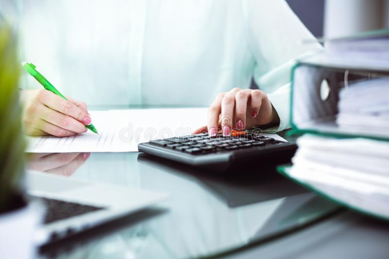 Bookkeeper or financial inspector making report, calculating or checking balance. Audit and tax service concept. Green. Colored image background royalty free stock photography