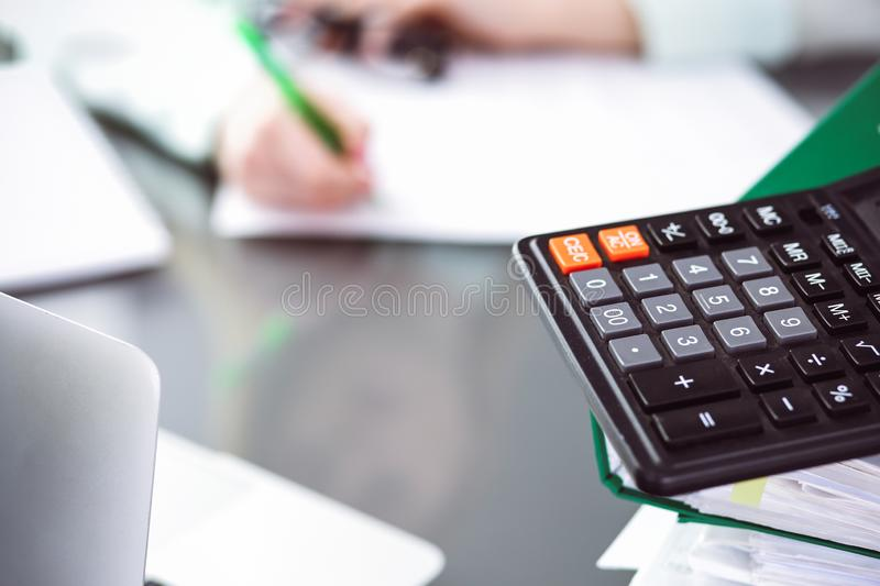 Bookkeeper or financial inspector making report, calculating or checking balance. Audit and tax service concept. Green. Colored image background royalty free stock photos