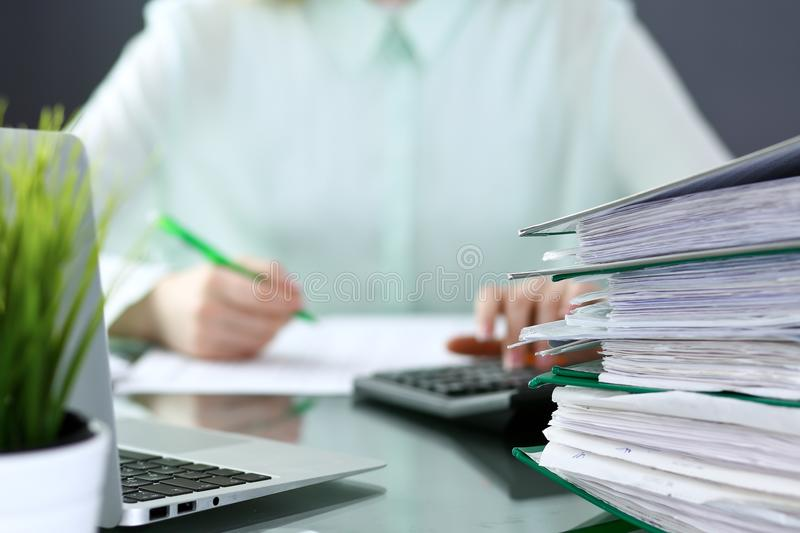 Bookkeeper or financial inspector making report, calculating or checking balance. Binders with papers closeup. Audit an royalty free stock photo