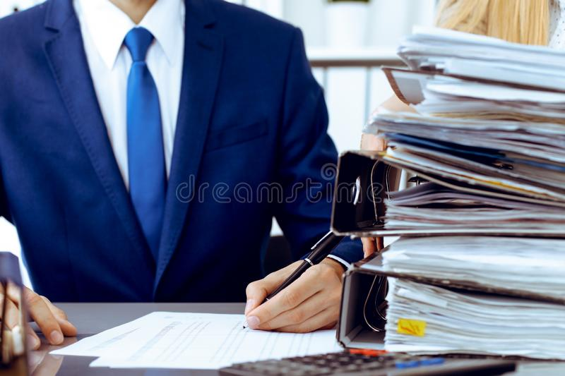 Bookkeeper or financial inspector and secretary making report, calculating or checking balance. Internal Revenue Service. Inspector checking financial document stock image