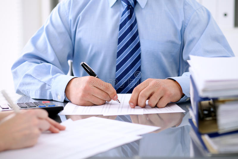 Bookkeepers or financial inspector making report, calculating or checking balance. Audit concept. Bookkeepers or financial inspector making report, calculating stock photo