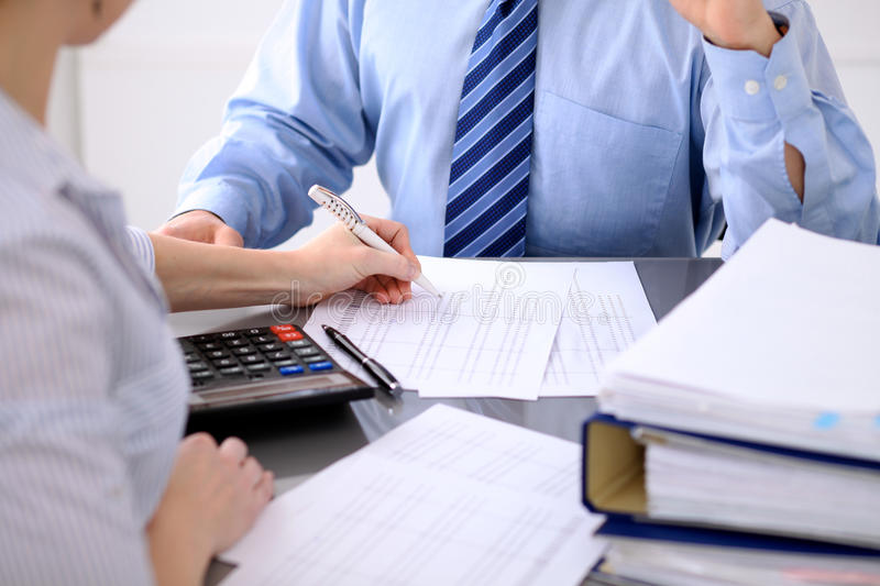 Bookkeepers or financial inspector making report, calculating or checking balance. Audit concept. Bookkeepers or financial inspector making report, calculating stock photos