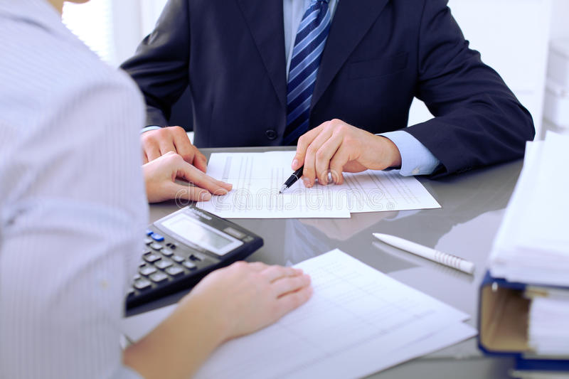 Bookkeepers or financial inspector making report, calculating or checking balance. Audit concept. Bookkeepers or financial inspector making report, calculating stock photography