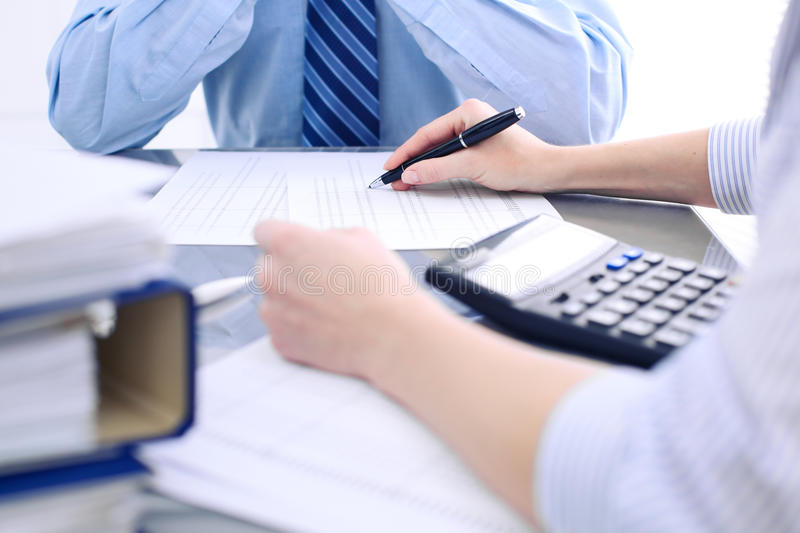 Bookkeepers or financial inspector making report, calculating or checking balance. Audit concept. Bookkeepers or financial inspector making report, calculating stock images
