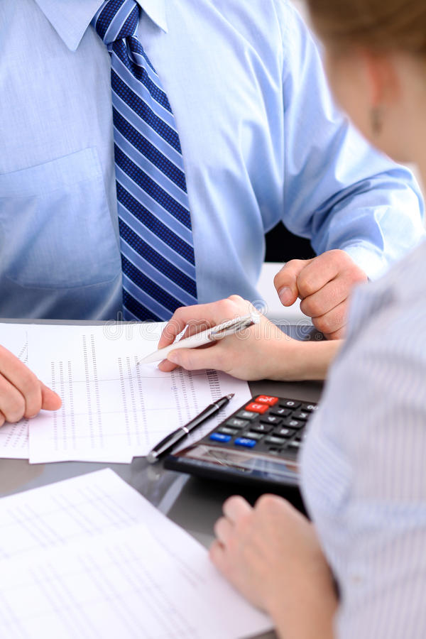 Bookkeepers or financial inspector making report, calculating or checking balance. Audit concept. Bookkeepers or financial inspector making report, calculating stock image