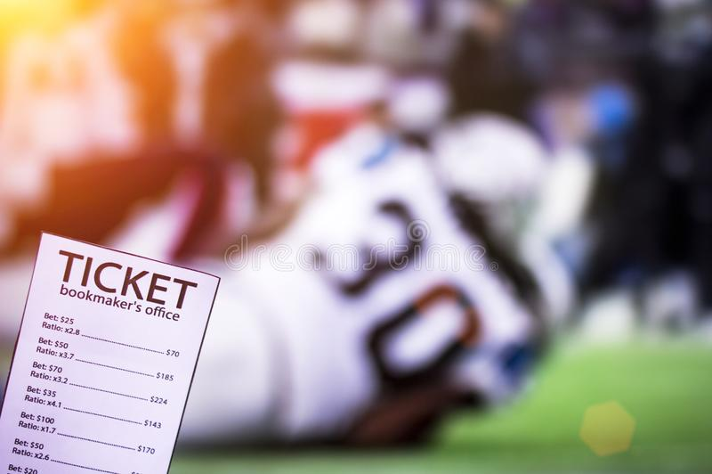 Bookmaker`s ticket, against the background of the TV on which American football is going, sports betting, play. Bookmaker`s ticket, against the background of the royalty free stock photography
