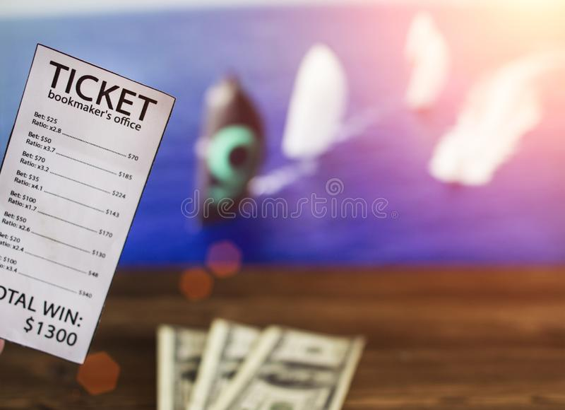 Bookmaker`s ticket and money dollars on the background of a TV on which show sailing, sports betting. Dollars royalty free stock photography