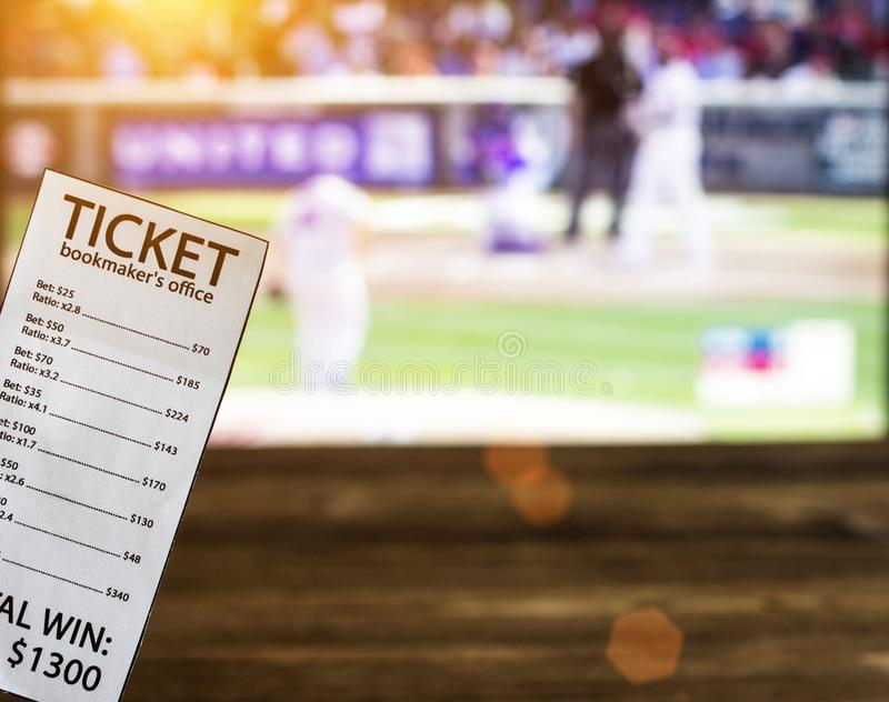 Bookmaker ticket on the background of a TV showing baseball, sports betting, bookmaker. Bookmaker ticket on the background of a TV showing baseball, sports stock photos