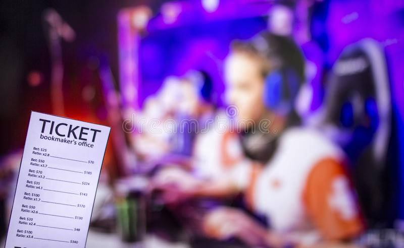 Bookmaker ticket on the background of a TV on which e-sports are shown, sports betting, Bookmaker ticket and cybersport. Bookmaker ticket on the background of a royalty free stock image