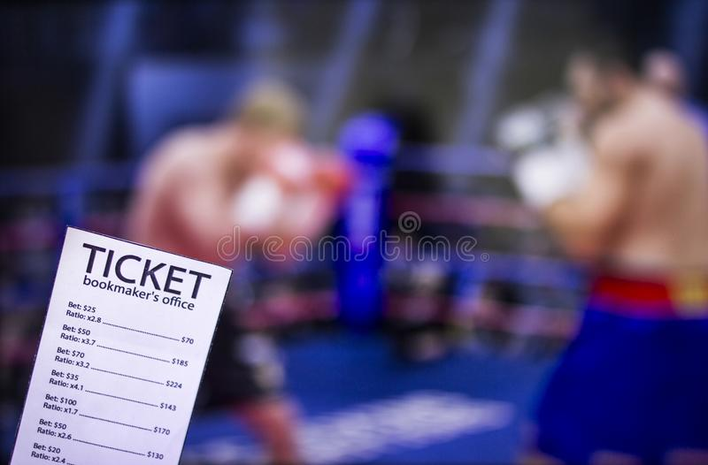 Bookmaker ticket on the background of the TV on which show boxing, sports betting, ring. Bookmaker ticket on the background of the TV on which show boxing royalty free stock images