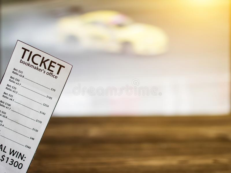 Bookmaker ticket on the background of the TV on which show drift on cars, sports betting, drift. Bookmaker ticket on the background of the TV on which show drift stock photography