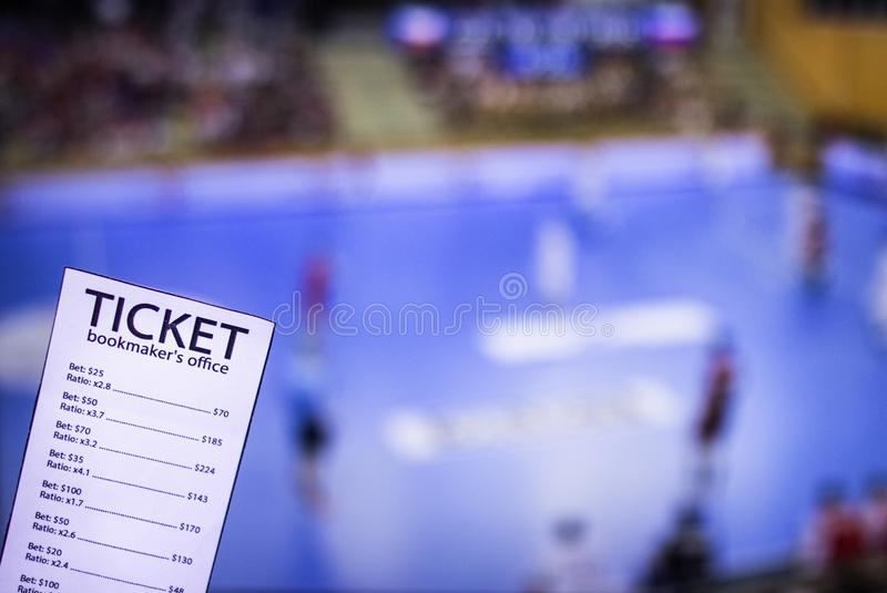Bookmaker ticket on the background of the TV on which show handball, sports betting, handball. Bookmaker ticket on the background of the TV on which show royalty free stock photo