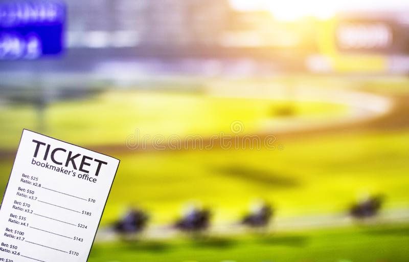 Bookmaker ticket on the background of the TV on which show jumps on horses, sports betting, bookmaker ticket. Bookmaker ticket on the background of the TV on stock photo