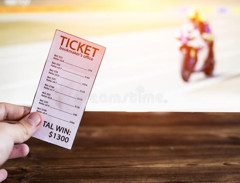Bookmaker ticket on the background of the TV on which show motorcycle racing, sports betting Bookmaker ticket and motorcycle races. Bookmaker ticket on the stock photography