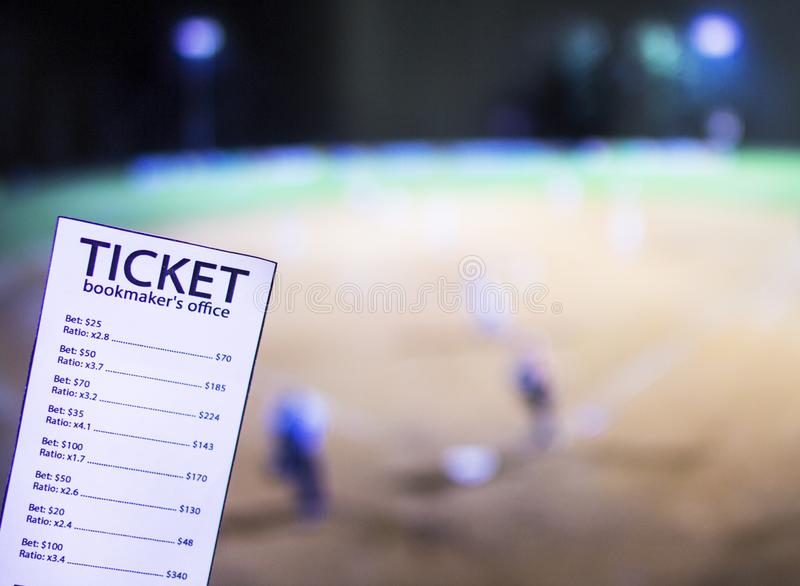 Bookmaker ticket on the background of the TV on which show a sports game softball, sports betting, softball. Bookmaker ticket on the background of the TV on royalty free stock image