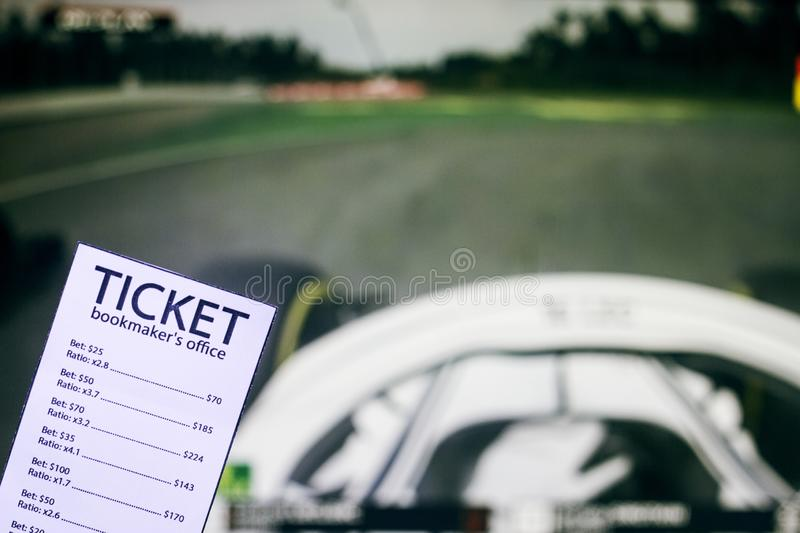 Bookmaker ticket on the background of the TV on which show the sports races the formula, sports betting, bookmaker. Bookmaker ticket on the background of the TV stock images