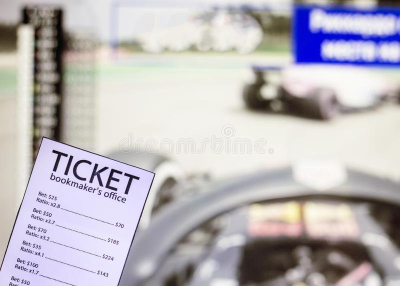 Bookmaker ticket on the background of the TV on which show the sports races the formula, sports betting, bookmaker. Bookmaker ticket on the background of the TV royalty free stock photography