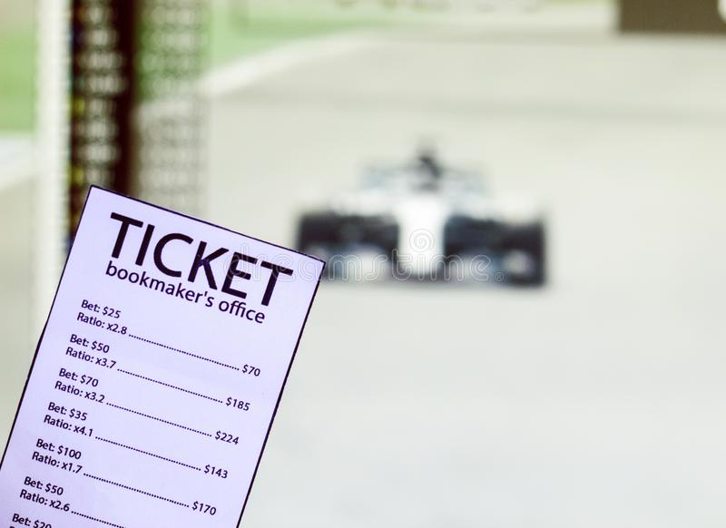 Bookmaker ticket on the background of the TV on which show the sports races the formula, sports betting, bookmaker. Bookmaker ticket on the background of the TV royalty free stock images