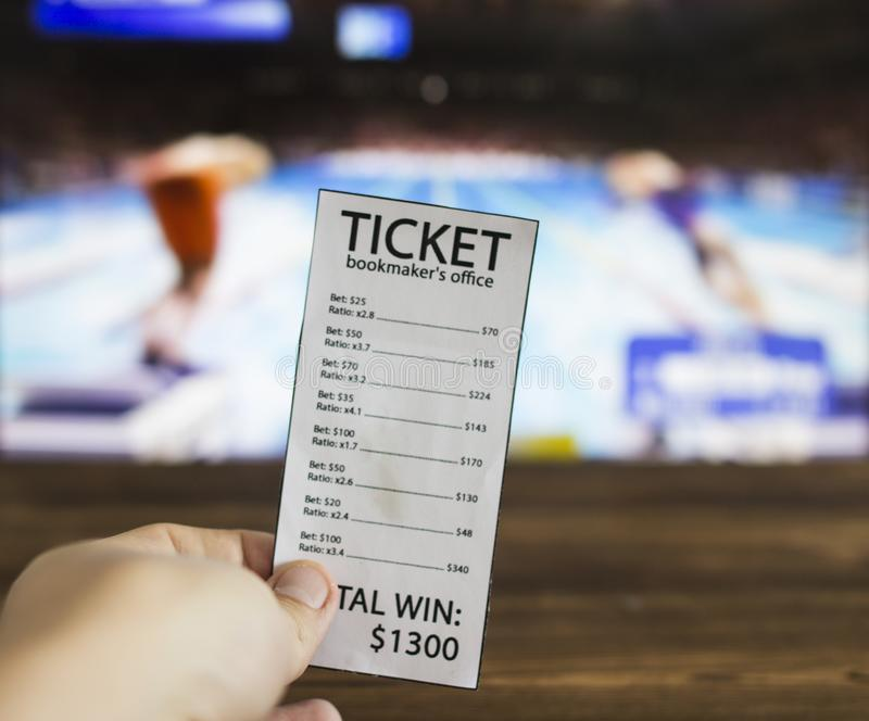 Bookmaker ticket on the background of TV on which show swimming, water sports, sports betting, bookmaker ticket. Bookmaker ticket on the background of TV on royalty free stock photos