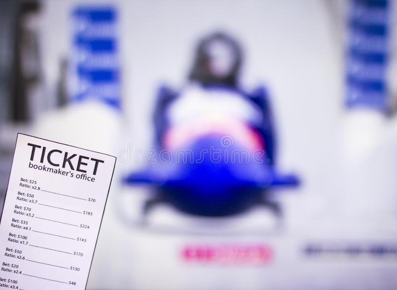 Bookmaker ticket on the background of the TV on which show toboggans, bobsled, sports betting. Bookmaker stock photos
