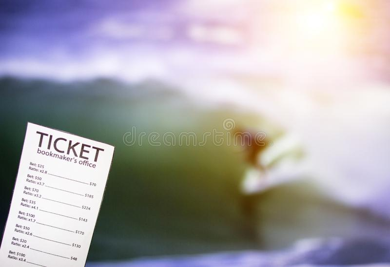 Bookmaker ticket on the background of the TV on which show water surfing, sports betting, bookmaker. Bookmaker ticket on the background of the TV on which show stock photography