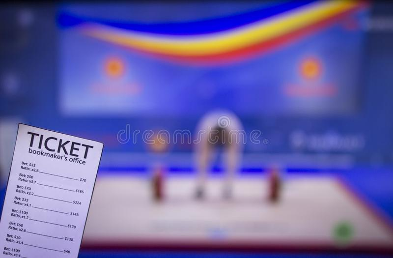 Bookmaker ticket on the background of TV on which show weightlifting, sports betting, barbell. Bookmaker ticket on the background of TV on which show royalty free stock photo
