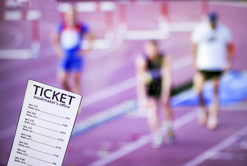 Bookmaker ticket on the background of the TV, which shows athletics, running, jumping, sports betting, Bookmaker ticket. Bookmaker ticket on the background of royalty free stock image