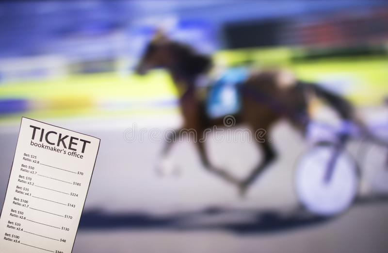 Bookmaker ticket on the background of the TV, which shows sport trotting, sports betting, bookmaker. Bookmaker ticket on the background of the TV, which shows stock photography