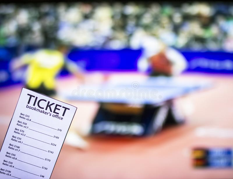 Bookmaker ticket on the background of the TV, which shows table tennis, sports betting, bookmaker ticket, ping-pong. Bookmaker ticket on the background of the TV royalty free stock photography